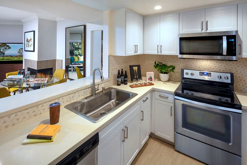 Interior view of kitchen and living room at The Villas of Renaissance Apartment Homes in San Diego, CA.