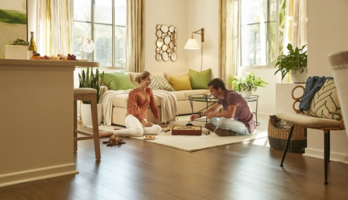 Interior view of couple playing board game in living room at Irvine Company Apartment Communities.
