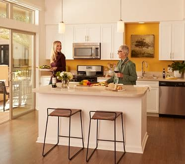 Interior view of women in kitchen at Irvine Company Apartment Communities.