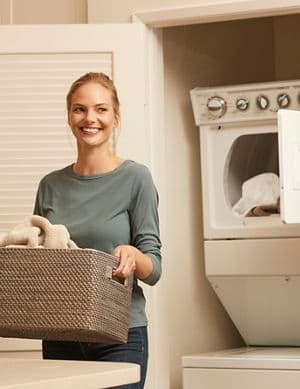 Interior view of woman holding a laundry basket in laundry room at Irvine Company Apartment Communities.
