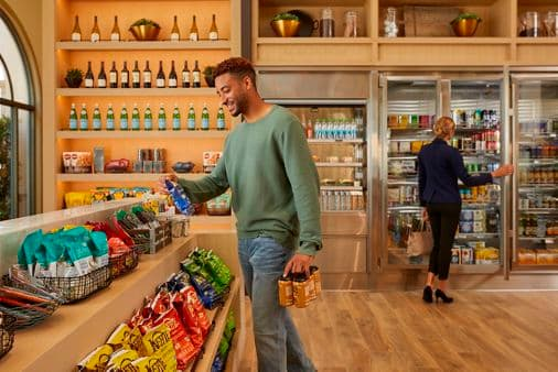 Interior view of people shopping at Cafe & Market at Promenade Apartment Homes in Irvine, CA.