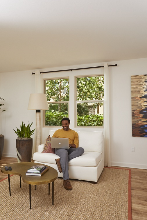 Man working from home in living room at an Irvine Company Apartment Community.