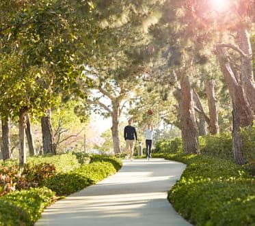 Exterior view of people walking on ped pathway at Paseo Westpark in Irvine, CA.