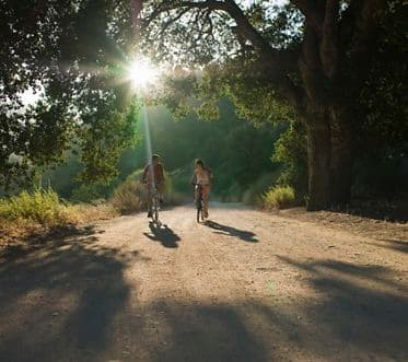young couple biking down dirt road
