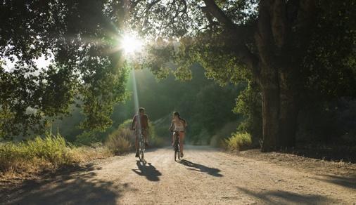 young couple biking down dirt road