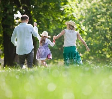 Family walking hand-in-hand in park