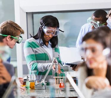 Multi-ethnic group of students with instructor in chemistry lab, wearing safety goggles, working with chemicals in test tubes and beakers.  Selective focus.