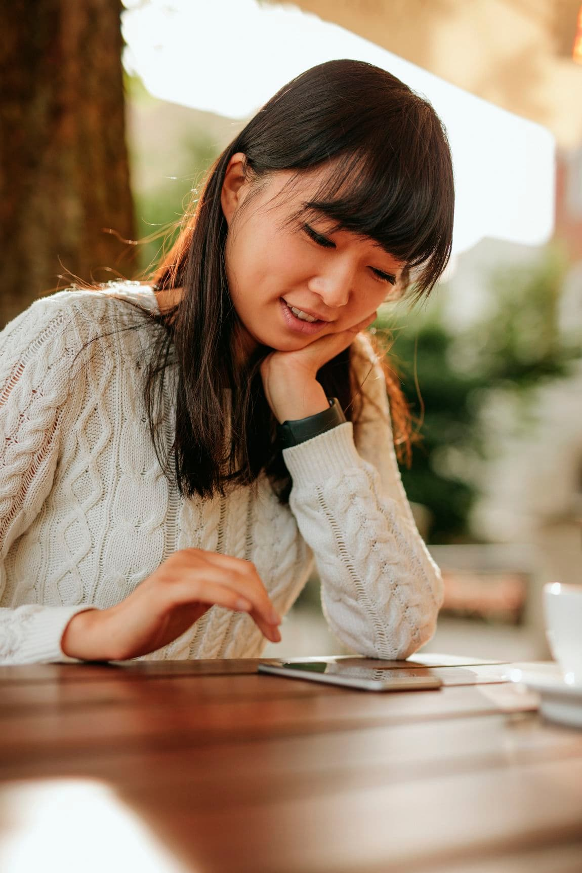 Beautiful chinese woman using cellphone at outdoor cafe. Asian female model using mobile phone at coffeeshop.