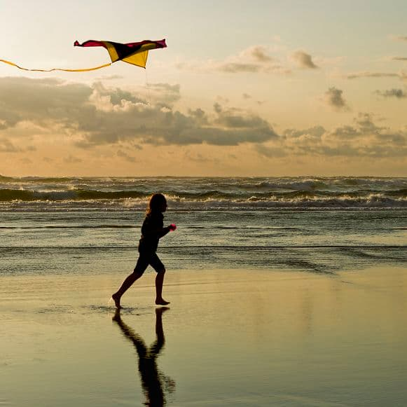 A girl flies a kite near sunset on the beach in Newport, Oregon.