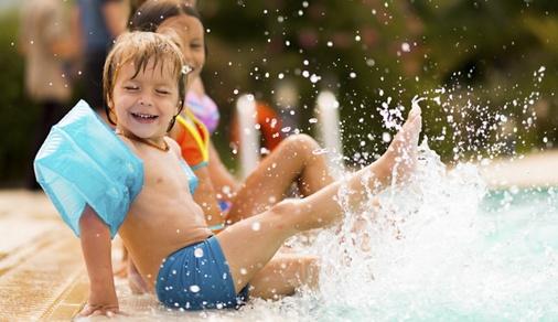 Kids in swimming pool have fun and splashing water