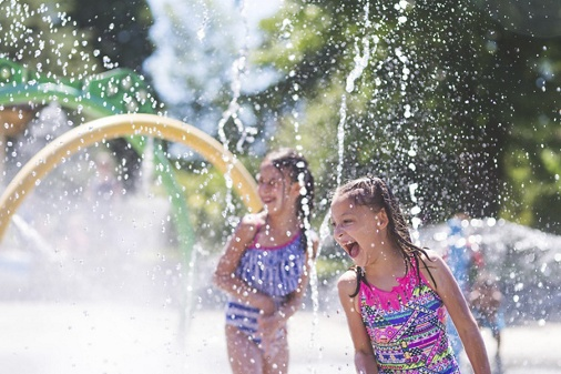 A group of young children frolic and run in a playground splash pad. It is a sunny, perfect day for getting wet and playing hard! Two young girls in swimsuits are running through the sprinklers and yelling and laughing as the water droplets cascade all around them.