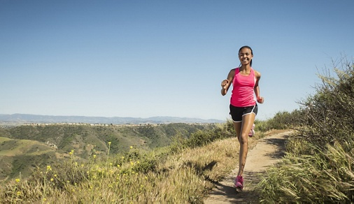 Mixed race girl running on hillside path