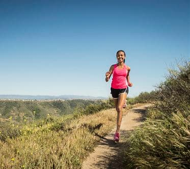 Mixed race girl running on hillside path