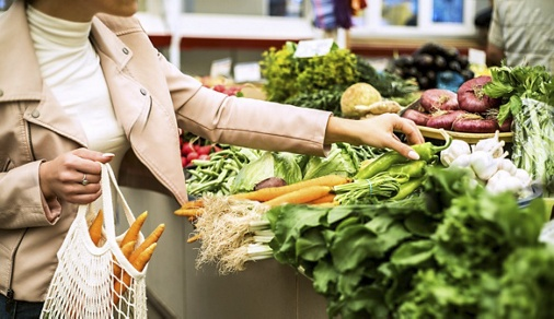 Woman choosing greenery and vegetables at farmer market and using reusable eco bag. Zero waste shopping concept.
