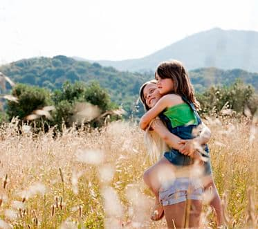 Girl carrying friend in field