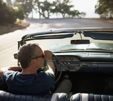 Man driving convertible car
