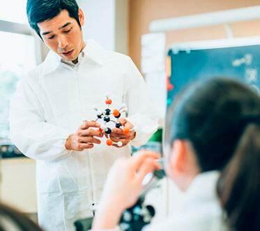 Teacher explaining molecules in Junior High school Science Lab using glucose molecular model and microscopes