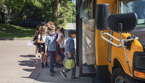 Group of elementary school kids getting in a yellow school bus. Multi-ethnic group, boys and girls age 8-9, with books, backpack and lunch boxes. A little boy is leading the pack, ready to get in the bus, the door is open. Horizontal outdoors shot with copy space. This was taken in Quebec, Canada.