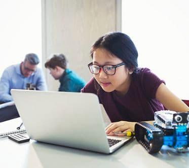 Focused girl student programming robotics at laptop in classroom