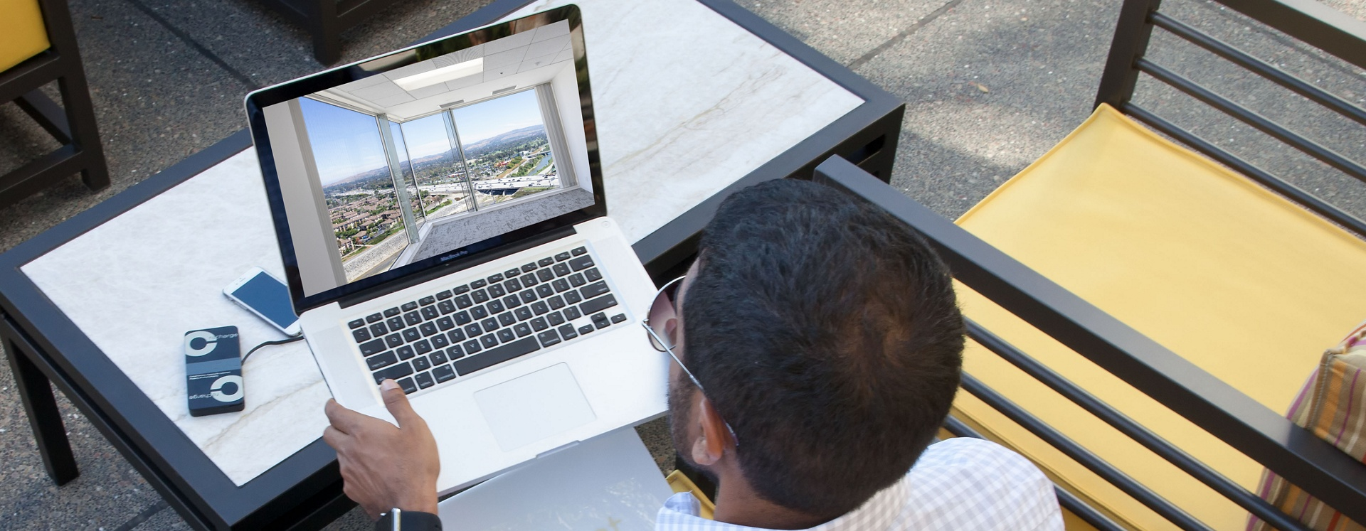 Image of man on laptop viewing a virtual tour for an Irvine Company Office.