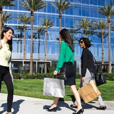 Lifestyle photography of 400 Spectrum Center Drive featuring people shopping at nearby Irvine Spectrum Center