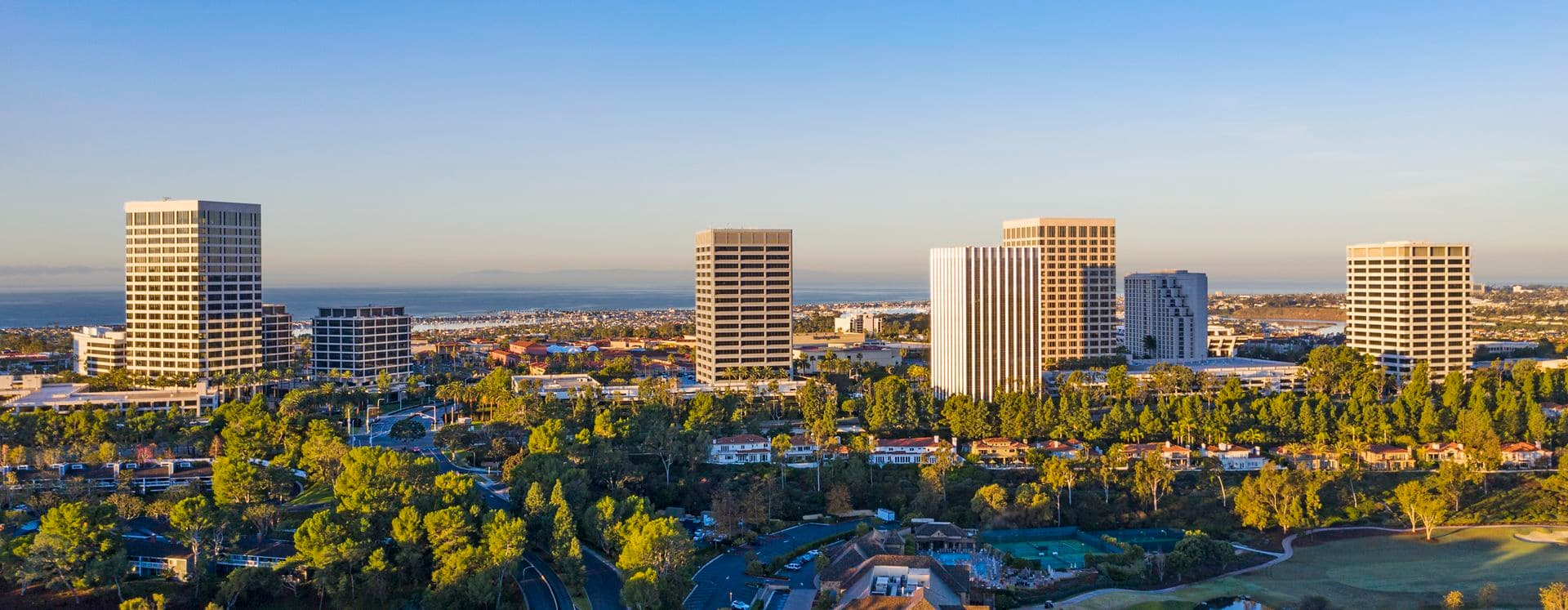 Aerial photography of the Newport Center area featuring snowy mountains in Newport Beach, CA