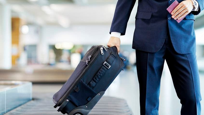 Mid section of a businessman collecting his luggage at baggage claim. Horizontal shot.