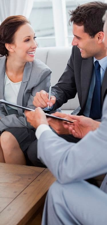 Businessman signing contract while looking at his partner